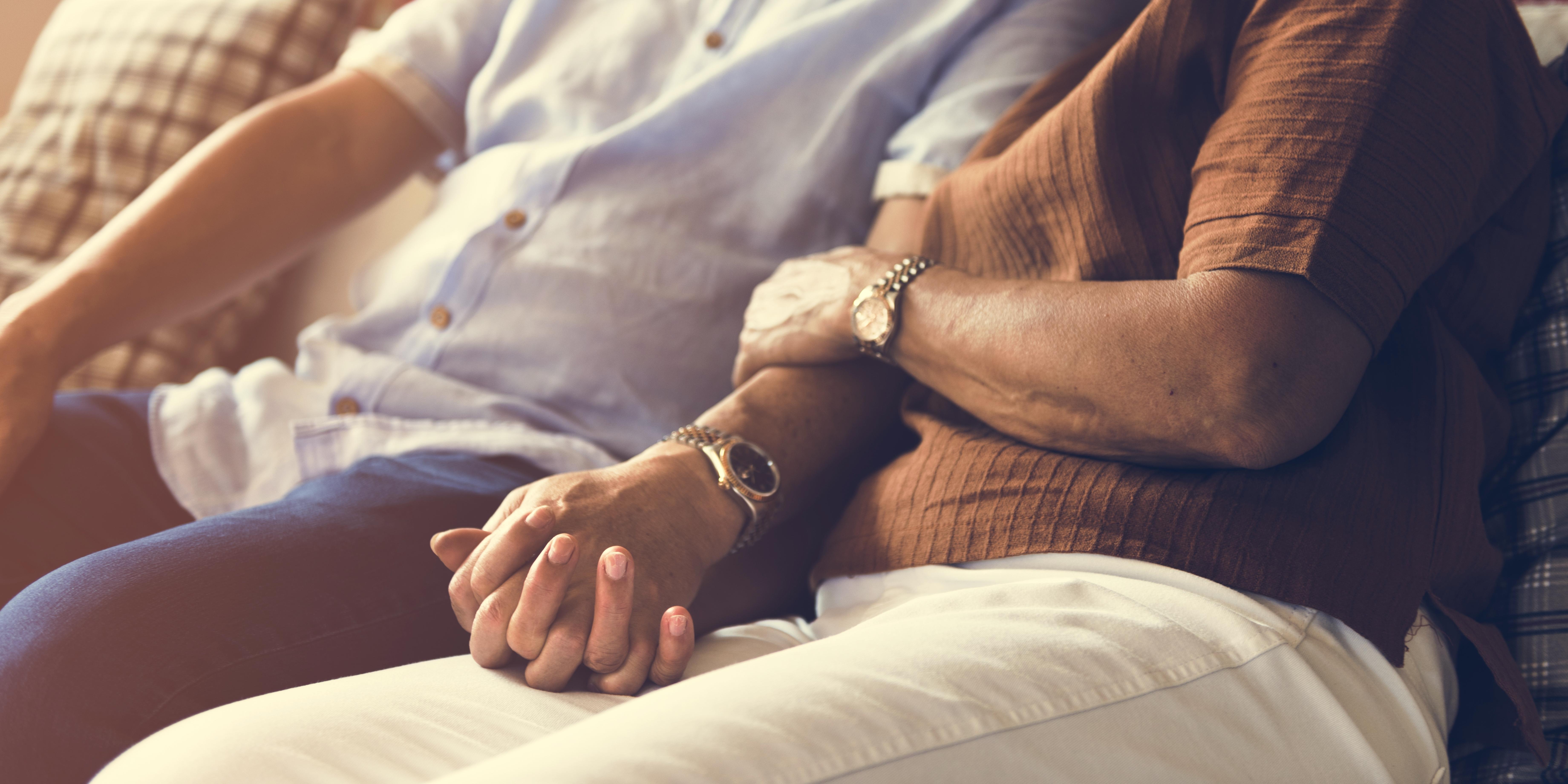 Una pareja cogida de la mano en el sofá de su casa